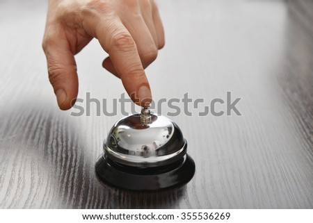 Male hand ringing in service bell on wooden table closeup