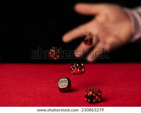 Male hand rolling five dice on red felt