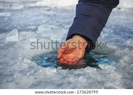 Male hand scoops water from the hole of the Lake Baikal - stock photo