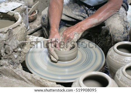 Male hand sculpting mud pot in pottery