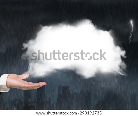Male hand showing white cloud with heavy rain dark cityscape background