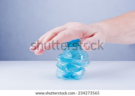 Male hand squashing an empty plastic bottle, close up. - stock photo