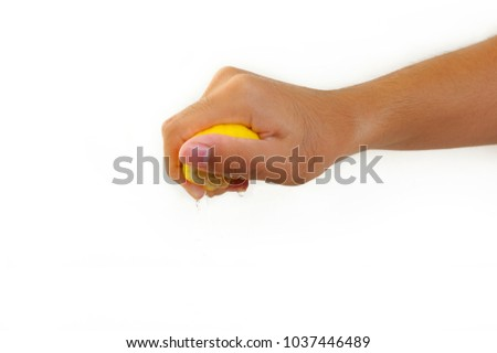 male hand squeezing lemon on white background