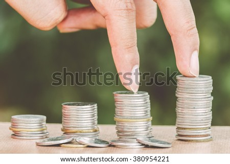 Male hand steps on money coin like stack growing business on green background - finance and money concept