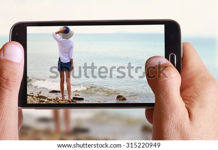 Male hand taking photo of Attractive Blonde Woman wearing white shirt and straw standing and enjoying view on the beach near sea with cell, mobile phone. - stock photo
