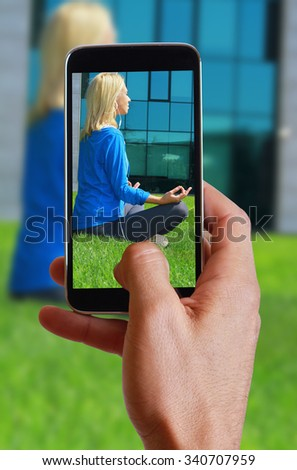 Male hand taking photo of Woman  meditating  in  City Central Park in yoga lotus pose with cell, mobile phone. Sport, fitness, active lifestyle , urban workout concept - stock photo
