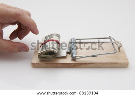 Male hand taking rolled up dollar bills from mousetrap - stock photo