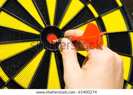 Male hand throwing dart arrow in bulls eye on dart board game - stock photo