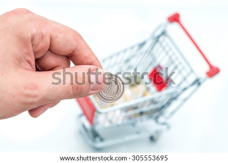 Male hand throws a coin into money box of the shape of trolley. The conception of how to cost-effective spend money while shopping. - stock photo