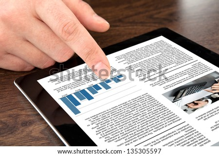 male hand touching computer tablet with business news on screen