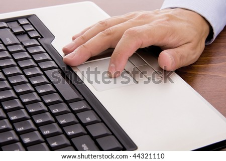 Male hand typing on a laptop - stock photo