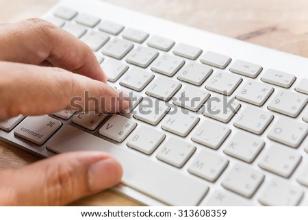 male hand typing on keyboard computer on wooden table,side view