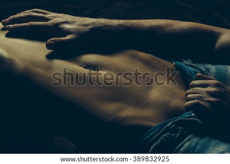 Male hand undressing young sensual woman with bare belly in torn blue sexy jeans lying in studio on dark background closeup, horizontal picture - stock photo
