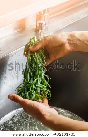 Male hand washing estragon. Herb under flow of water. Aroma of fresh herbs. Special seasoning for food. - stock photo