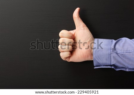 Male hand wearing a business shirt giving the thumbs up sign against a blank blackboard with copy space - stock photo