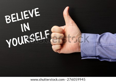 Male Hand wearing a business shirt giving the thumbs up sign for the phrase Believe In Yourself in white text on a blackboard  - stock photo