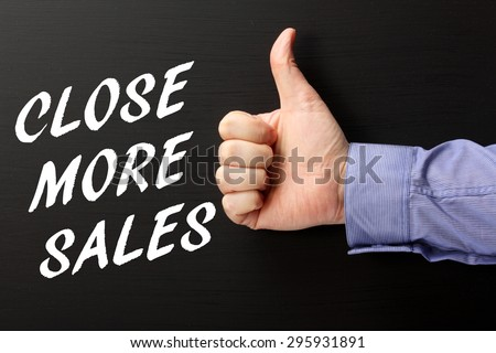 Male hand wearing a business shirt giving the thumbs up sign to the phrase Close More Sales in white text on a blackboard - stock photo