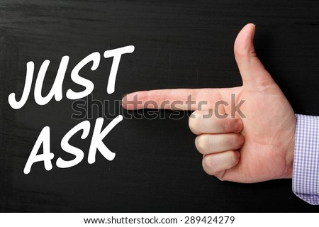 Male hand wearing a business shirt pointing a finger at the phrase Just Ask in white text on a blackboard - stock photo