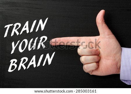Male hand wearing a business shirt pointing a finger at the phrase Train Your Brain in white text on a blackboard - stock photo