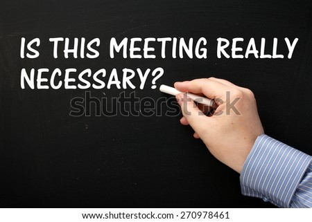 Male hand wearing a business shirt writing the question Is This Meeting Really Necessary on a blackboard. - stock photo