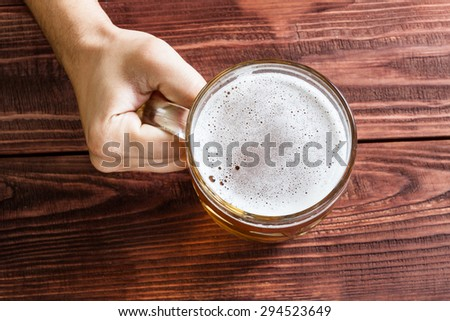 Male hand with a glass of beer, pub interior.