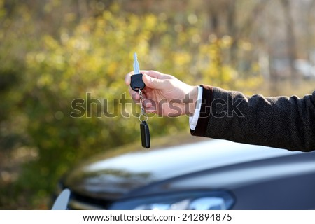 Male hand with car key on car background
