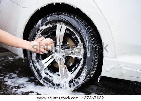 male hand with foam sponge washing car wheel - stock photo
