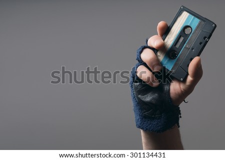 male hand with glove holding an old music tape - stock photo