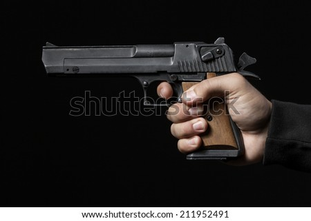 male hand with gun isolated on black background - stock photo