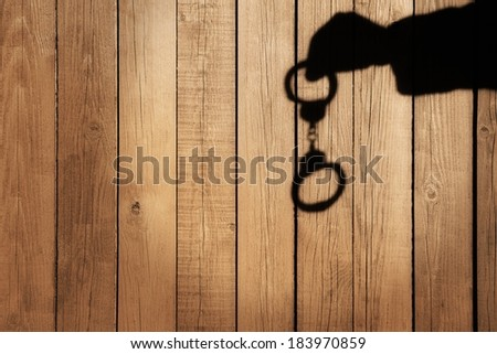 Male Hand with Handcuffs on Natural Wood Background. You can see more silhouettes and shadows on my page. - stock photo