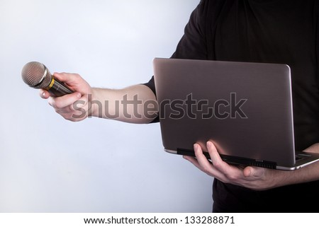 Male hand with microphone and notebook - stock photo