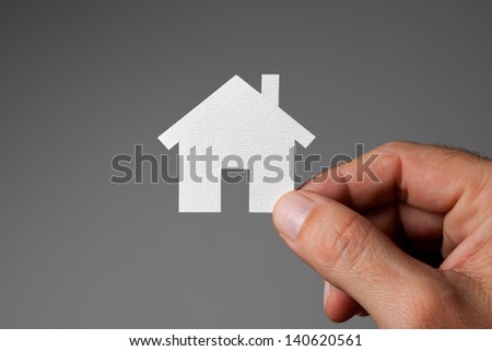 Male hand with model house. - stock photo