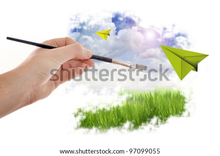 MAle hand with paint brush painting a beautiful summer landscape with blue sky and clouds - stock photo
