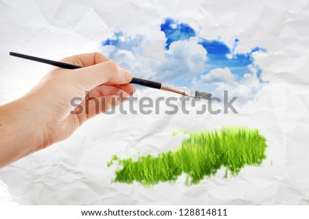 Male hand with panit brush painting a beautiful summer landscape with blue sky and clouds - stock photo
