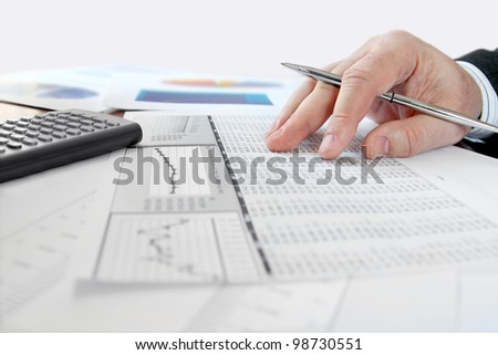 Male hand with pen analyzing  financial data - stock photo