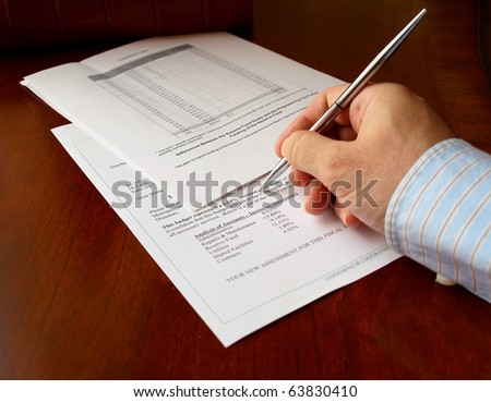 male hand with pen on the budget document - stock photo