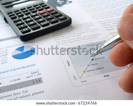 Male hand with pen on the investment chart with calculator - stock photo