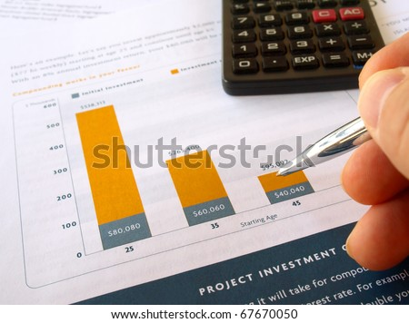 Male hand with pen on the project investment chart with calculator - stock photo