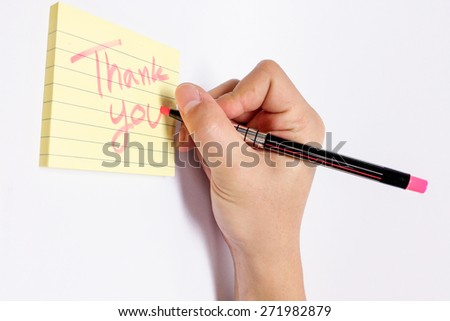 Male Hand with Pink Fluorescent Marker Writing Thank You Word in Yellow Sticky Notebook with Line - stock photo