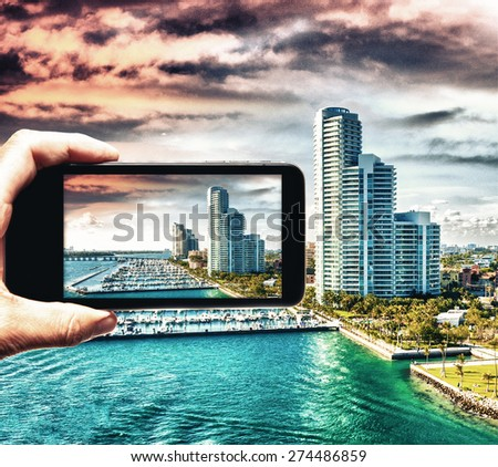 Male hand with smartphone taking a picture of Miami from cruise ship. Tourism concept. - stock photo
