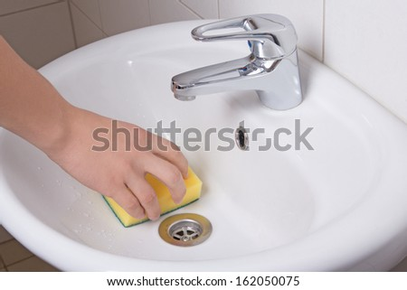 Male hand with yellow sponge cleaning white sink - stock photo