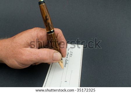 male hand writing check to IRS for Too many dollars - stock photo