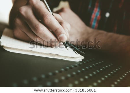 male hand writing in notebook with pen - stock photo