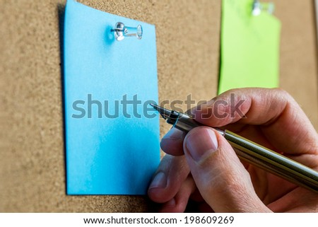 Male hand writing on blank sheet of blue paper with copyspace pinned up on a cork bulletin board. - stock photo