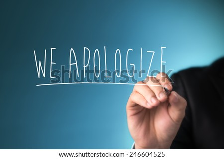 Male hand writing phrase we apologize you on virtual screen. - stock photo