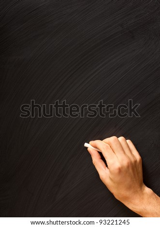Male hand writing with chalk on a clean blackboard - add your own chalk! - stock photo
