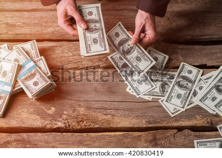Male hands counting dollars. Cash on brown wooden background. All you have earned. Good reward for a businessman. - stock photo