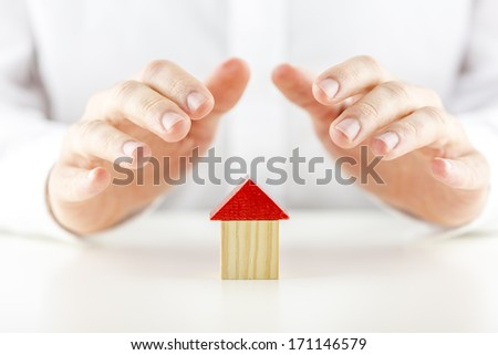 Male hands covering and protecting a small wooden model of a house or home conceptual of ownership, safety, insurance and security - stock photo