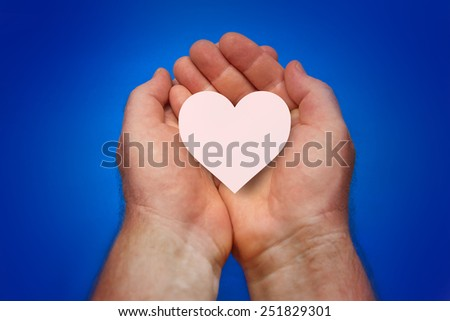 Male hands folded in a cup and holded aheart on a blue background - stock photo