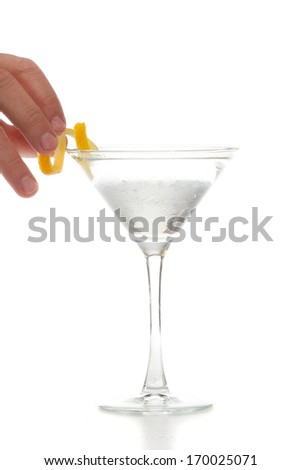male hands garnishing a vodka martini with a lemon twist - stock photo